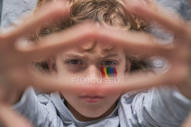 Top view of unhappy boy with colorful rainbow under eye showing stop gesture with hands with stay home inscription to the camera while lying on pillow and blanket on floor — Stock Photo