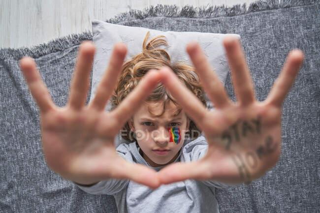 Draufsicht des unglücklichen Jungen mit buntem Regenbogen unter dem Auge, der Stopp-Geste mit Händen mit der Aufschrift