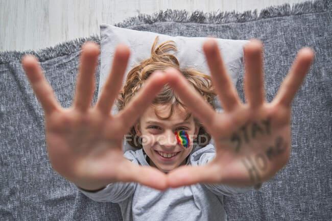 Visão superior do menino feliz com arco-íris colorido sob o olho mostrando gesto de parada com as mãos com ficar em casa inscrição para a câmera enquanto deitado no travesseiro e cobertor no chão — Fotografia de Stock
