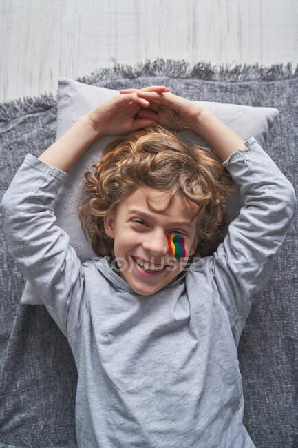 Visão superior do menino feliz com arco-íris sob os olhos deitado em cobertor e travesseiro e rindo enquanto fica em casa durante a quarentena — Fotografia de Stock
