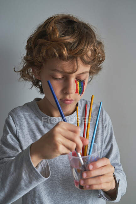 Focused boy with rainbow on face washing brush in cup of water while standing against gray background and painting during quarantine — Stock Photo