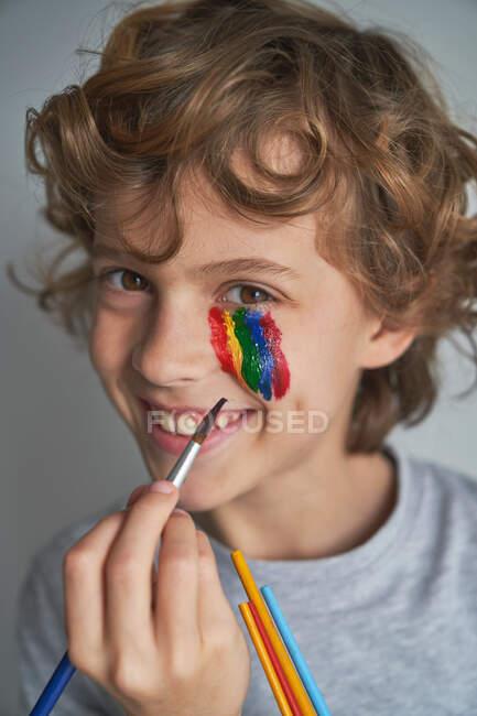 Happy boy pintura arco-íris colorido sob os olhos e olhando para a câmera enquanto ficar em casa durante a pandemia — Fotografia de Stock