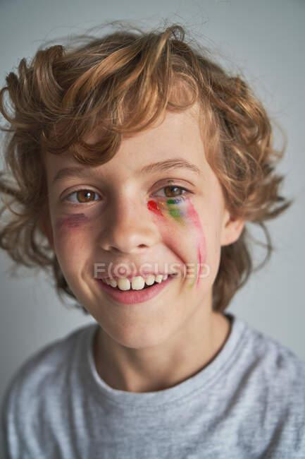 Alegre chico rubio con el arco iris desvaneciéndose bajo los ojos sonriendo mirando a casa durante la cuarentena - foto de stock