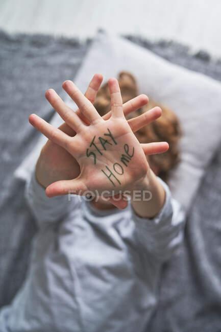 Von oben unkenntlich Junge zeigt Hand mit Stay Home-Schrift, während er während der Pandemie auf Decke und Kissen liegt — Stockfoto