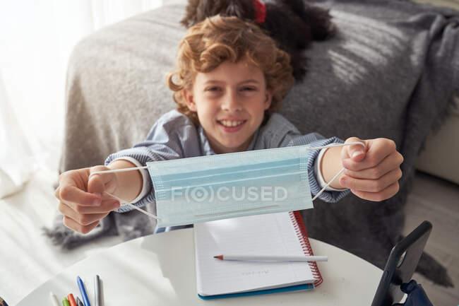 Сверху счастливый мальчик демонстрирует медицинскую маску на камеру, сидя за столом с ноутбуком и смартфоном и изучая онлайн во время карантина — стоковое фото
