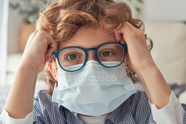 Smart boy in medical mask and glasses looking at camera while spending time at home during quarantine — Stock Photo