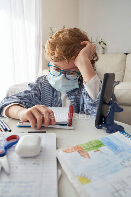 Exhausted smart boy in glasses and medical mask doing homework assignment while sitting at table and studying remotely during quarantine at home — Stock Photo