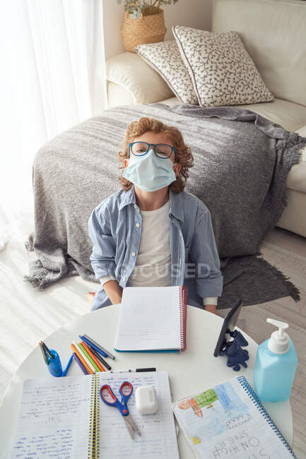 Boy in medical mask making notes in notepad while sitting at table with smartphone and disinfectant and studying online during quarantine — Stock Photo