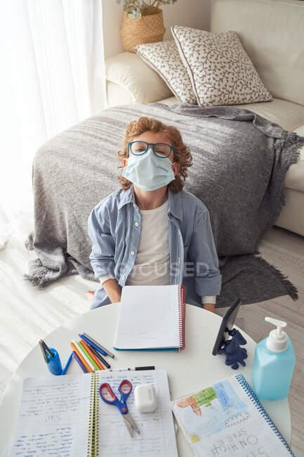 Junge in medizinischer Maske macht Notizen im Notizblock, während er mit Smartphone und Desinfektionsmittel am Tisch sitzt und während der Quarantäne online lernt — Stockfoto