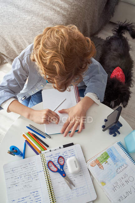Boy with curly hair sitting on sofa near round table and writing in notebook while doing homework in cozy living room at home — Stock Photo