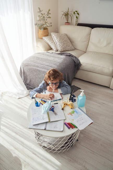 Menino fazendo anotações no bloco de notas enquanto sentado à mesa com smartphone e desinfetante e estudando on-line durante a quarentena — Fotografia de Stock