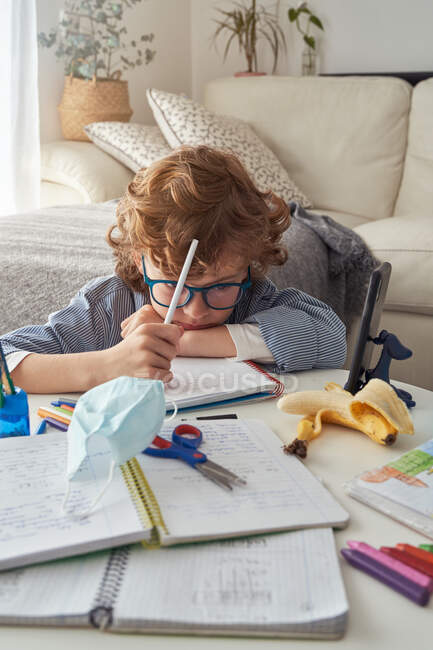 Clever boy in glasses keeping head on messy table and thinking over assignment during online lesson at home — Stock Photo
