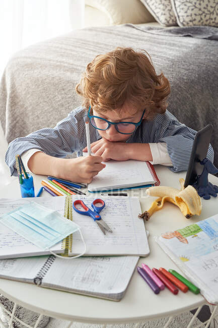 Boy making notes in notepad while sitting at table with smartphone and disinfectant and studying online during quarantine — Stock Photo