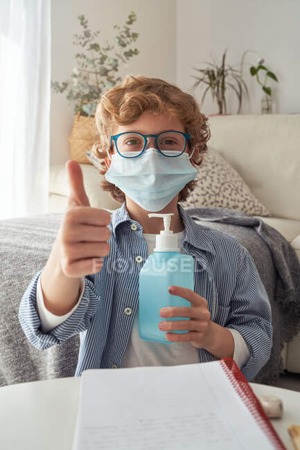 Boy in medical mask applying sanitizer on hands while sitting near sofa during quarantine at home — Stock Photo