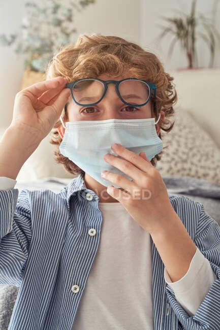 Kluger Junge in medizinischer Maske setzt Brille auf, während er am Tisch mit Notizbuch sitzt und sich zu Hause auf Fernstudien vorbereitet — Stockfoto