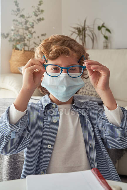 Smart boy in medical mask putting on glasses while sitting near table with notebook and preparing for remote studies at home — Stock Photo