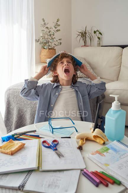 Menino com livro didático na cabeça sentado perto da mesa bagunçada e bocejo ao fazer lição de casa na acolhedora sala de estar durante a quarentena — Fotografia de Stock
