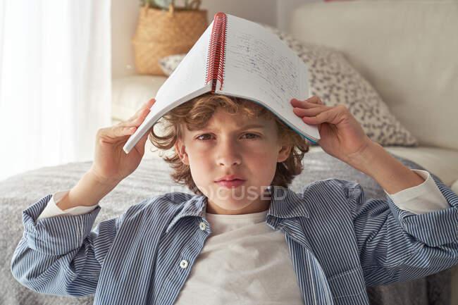Мальчик с учебником на голове сидит возле грязного стола и зевает во время выполнения домашней работы в уютной гостиной во время карантина — стоковое фото