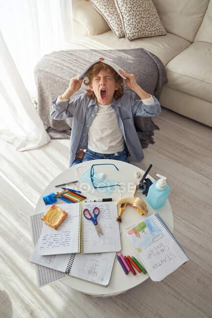 Сверху мальчик с учебником на голове сидит возле грязного стола и зевает во время выполнения домашней работы в уютной гостиной во время карантина — стоковое фото