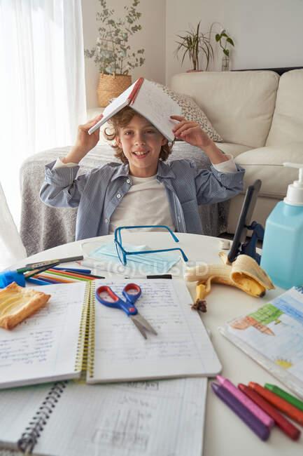 Garçon avec manuel sur la tête assis près de la table salissante et bâillant tout en faisant des devoirs dans le salon confortable pendant la quarantaine — Photo de stock