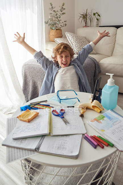 Excited boy cheering with raised arms while sitting at messy table in end of online lesson during quarantine at home — Stock Photo