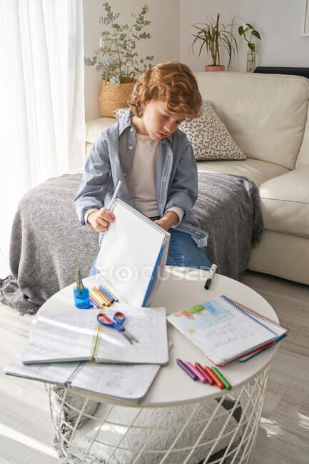 Garçon avec les cheveux bouclés assis sur le canapé près de la table ronde et l'écriture dans le carnet tout en faisant des devoirs dans le salon confortable à la maison — Photo de stock