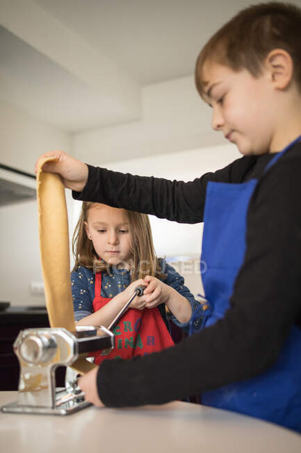 Uma menina com irmão mais velho usando máquina de massas enquanto prepara macarrão caseiro na cozinha doméstica — Fotografia de Stock