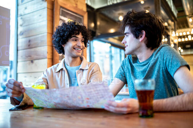 From below multiethnic young homosexual men with direction navigation map and fresh drinks smiling looking at each other while sitting at cafe table during romantic date — Stock Photo