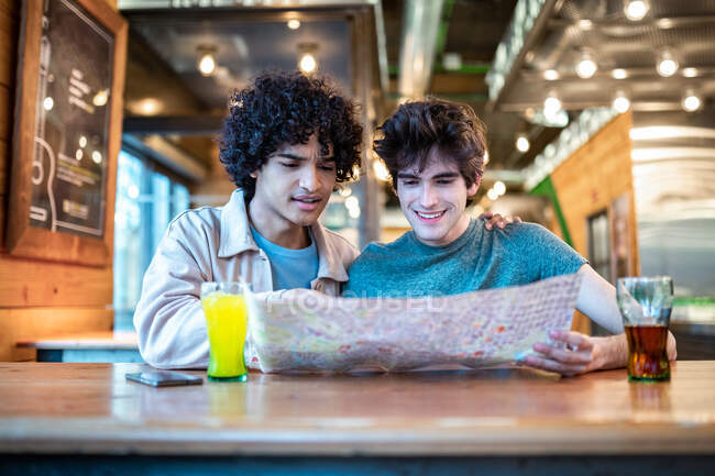 Multiethnic young homosexual men looking at direction navigation map and fresh drinks smiling while sitting at cafe table during romantic date — Stock Photo