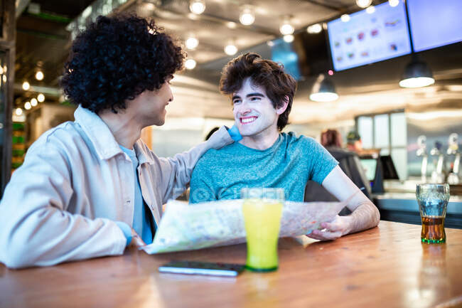 Multiethnic young homosexual men with direction navigation map and fresh drinks smiling looking at each other while sitting at cafe table during romantic date — Stock Photo