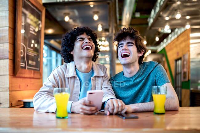 Мультиэтнические молодые гомосексуальные мужчины просматривают социальные сети на смартфоне и пьют свежие напитки, улыбаясь с закрытыми глазами, сидя за столиком кафе во время романтического свидания — стоковое фото
