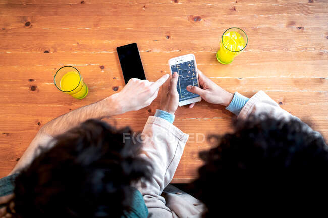 From above unrecognizable multiethnic young homosexual men browsing social media on smartphone and having fresh drinks smiling while sitting at cafe table during romantic date — Stock Photo