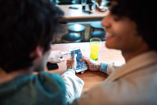 Back view of unrecognizable multiethnic young homosexual men browsing social media on smartphone and having fresh drinks smiling while sitting at cafe table during romantic date — Stock Photo