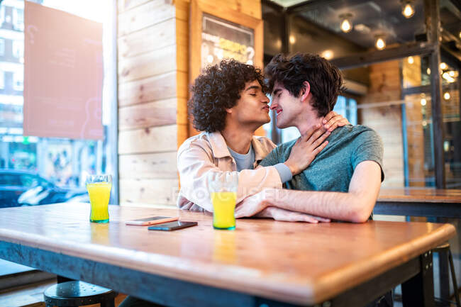 Side view of excited ethnic men embracing each other with closed eyes on table and laughing during romantic date in modern cafeteria — Stock Photo