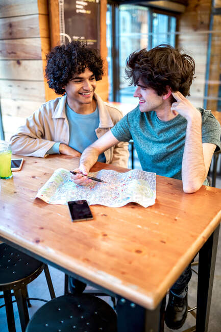 From above multiethnic young homosexual men with direction navigation map and fresh drinks smiling looking at each other while sitting at cafe table during romantic date — Stock Photo