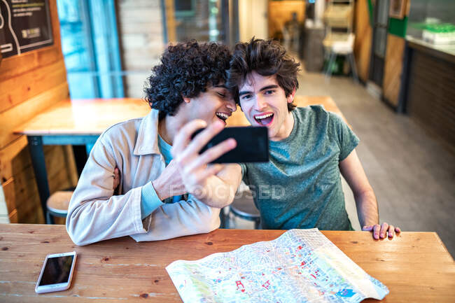 Multiethnic young homosexual men taking a selfie photo on smartphone and having fresh drinks smiling while sitting at cafe table during romantic date — Stock Photo