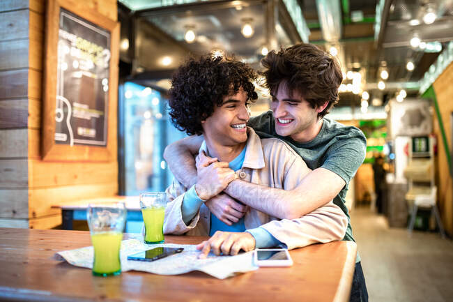 Мультиэтнические молодые гомосексуальные мужчины обнимают друг друга, глядя на навигационную карту и выпивая свежие напитки, улыбаясь, сидя за столиком кафе во время романтического свидания — стоковое фото