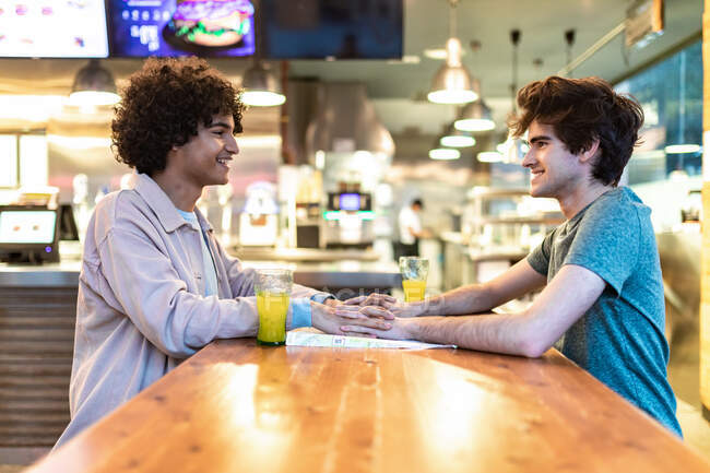 Side view of excited ethnic men embracing each other holding hands over table and laughing during romantic date in modern cafeteria — Stock Photo