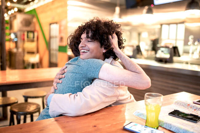 Excited ethnic men embracing each other with closed eyes on table and laughing during romantic date in modern cafeteria — Stock Photo