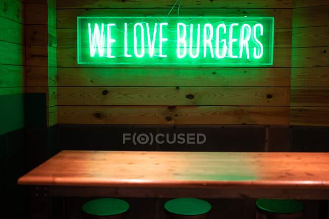 Ярко-зеленый Мы любим гамбургеры знак светится неоновый свет над деревянным столом в вечернее время в современном кафетерии — стоковое фото