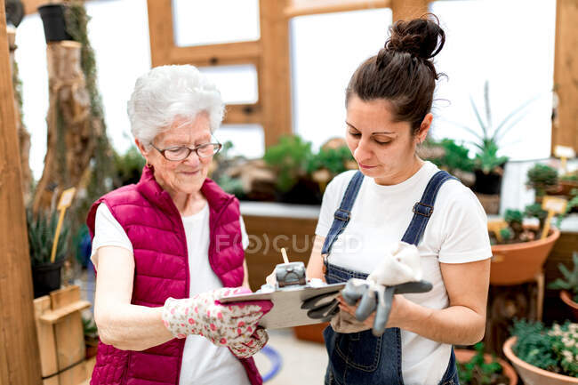 Adult woman writing on clipboard near elderly colleague while working in hothouse together — Stock Photo