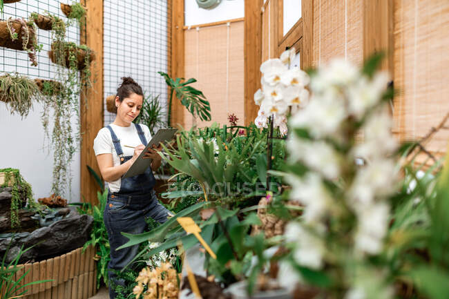 Side view of adult woman writing on clipboard while standing near plant with white flowers during work in hothouse — Stock Photo