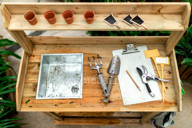 From above top view various gardening instruments placed on lumber table in hothouse — Stock Photo
