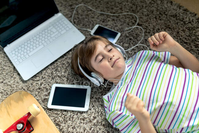 From above of cheerful little boy in casual shirt listening to music with headphones while lying on carpet near gadgets and skateboard in bedroom — Stock Photo
