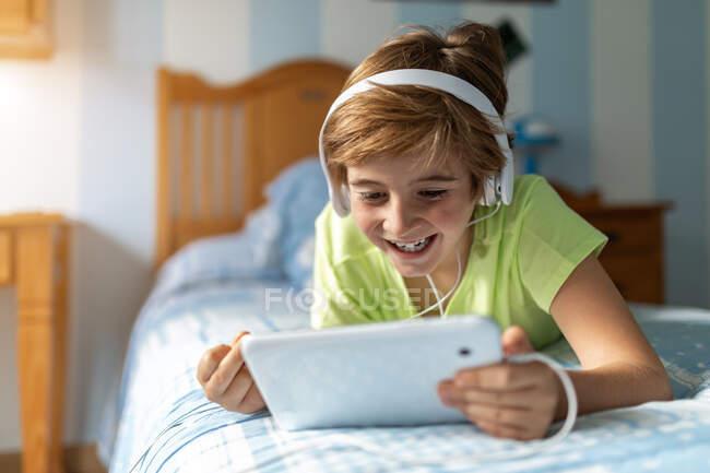 Préadolescent positif en tenue décontractée avec écouteurs couchés sur le lit et regarder un film sur tablette tout en se reposant à la maison — Photo de stock