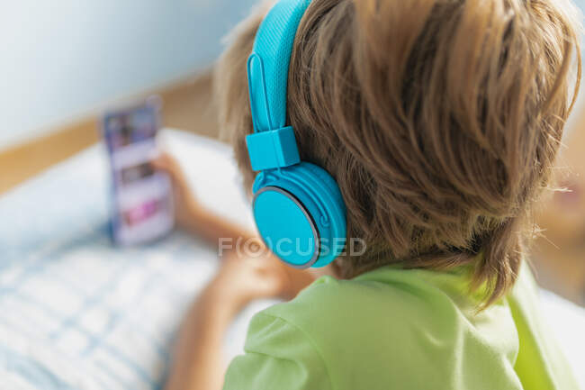 Ragazzo con vista posteriore in abbigliamento casual con cuffie sdraiato sul letto e guardare film su smartphone mentre si riposa a casa — Foto stock