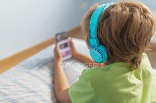 Visão traseira menino em desgaste casual com fones de ouvido deitado na cama e assistindo filme no smartphone enquanto descansa em casa — Fotografia de Stock