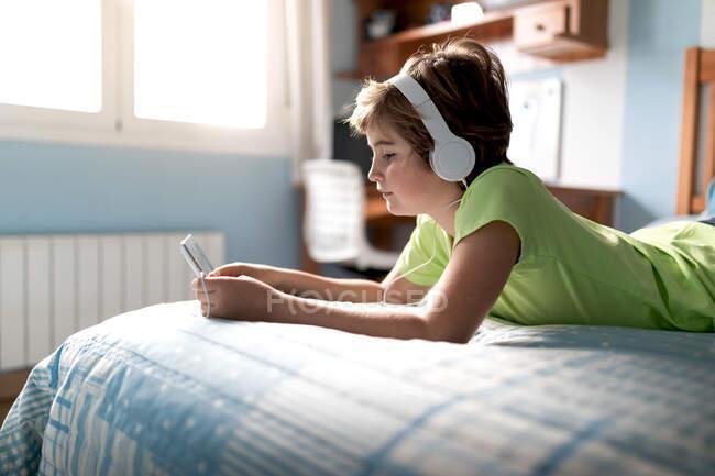 Positivo ragazzo preadolescente in abbigliamento casual con cuffie sdraiato sul letto e guardare film su tablet mentre si riposa a casa — Foto stock