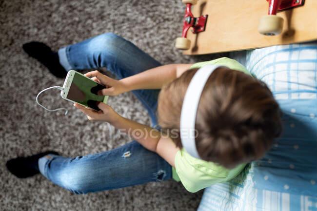 Bambino con le cuffie che ascolta musica e chatta con gli amici sui social network mentre siede vicino allo skateboard in camera da letto — Foto stock