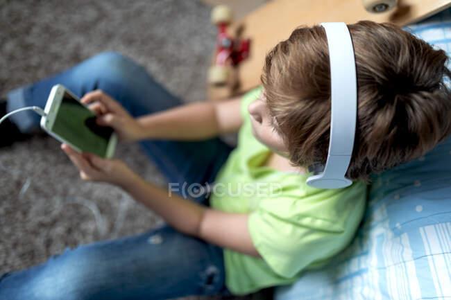 Petit garçon avec écouteurs écouter de la musique et bavarder avec des amis dans le réseau social tout en étant assis près de planche à roulettes dans la chambre — Photo de stock